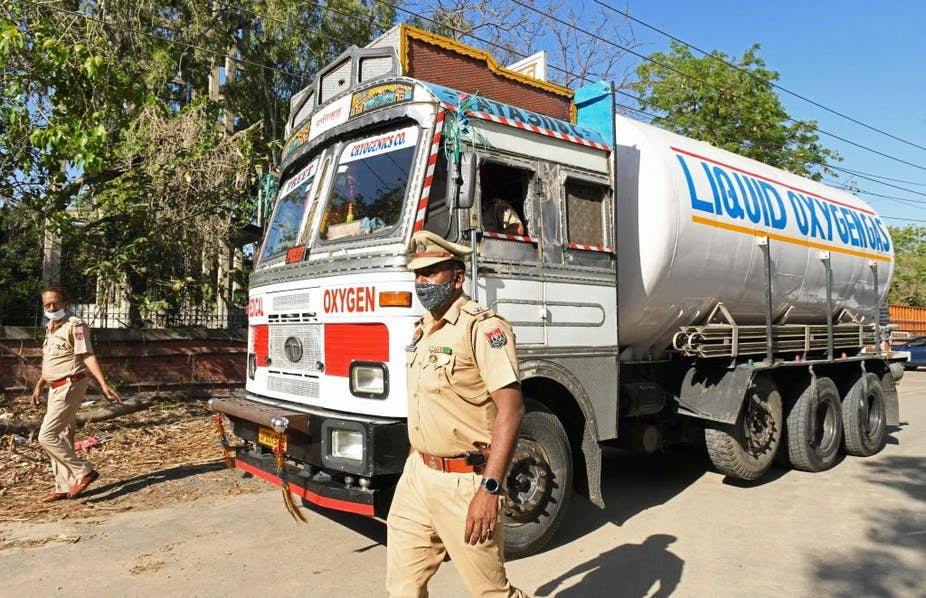 Police personnel escort a truck carrying medical liquid oxygen