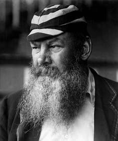 Man with large beard and wearing a striped hat.