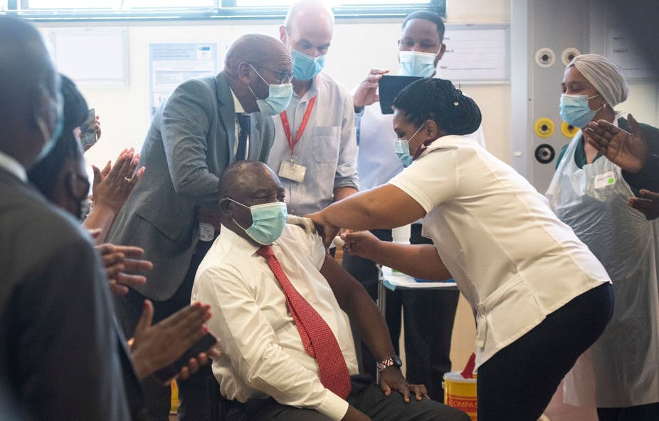 A seated man wearing a mask, with one shirt sleeve rolled up, receives an injection from a woman in nurse's uniform while other masked people look on