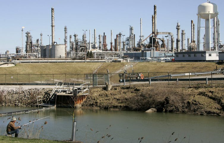 A man fishes next to a refinery south of Sarnia, Ont.