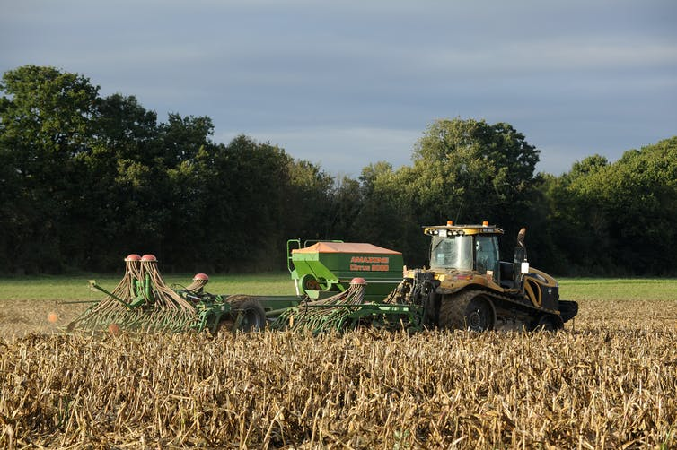 A tractor with a mechanised seed drill in tow prepares a field for sowing.