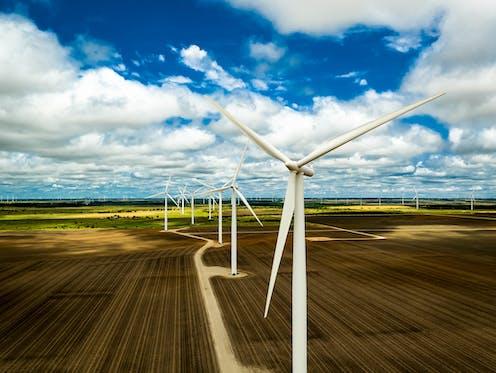 Wind turbines sit on a farm.