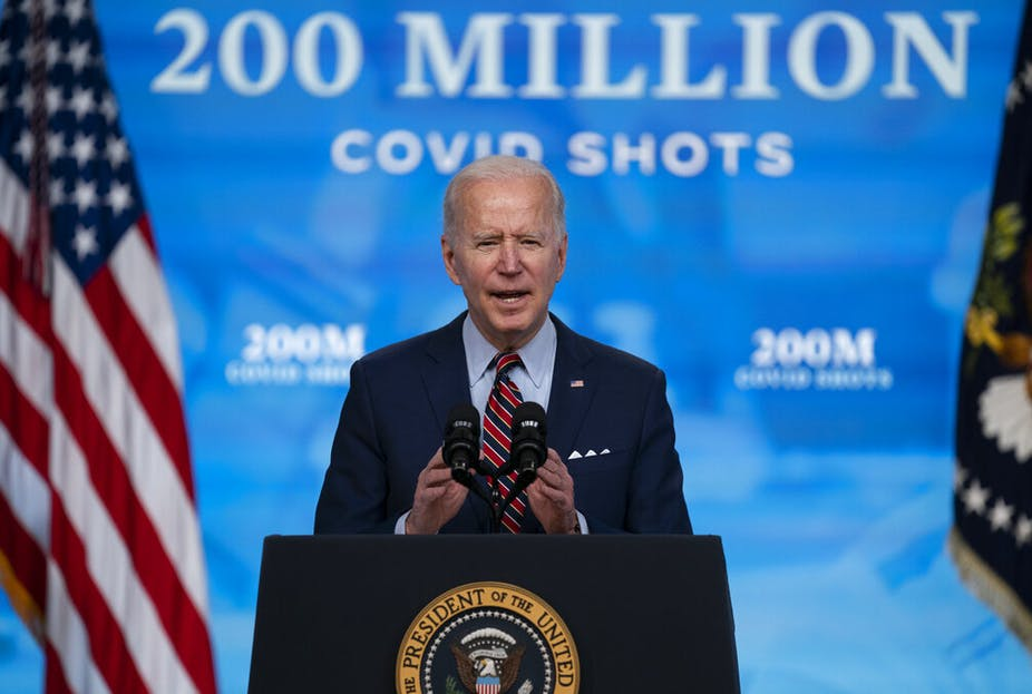President Joe Biden speaks from a lecturn decorated with the US presidential seal. Behind him a backdrop reads: 200 million covid shots.