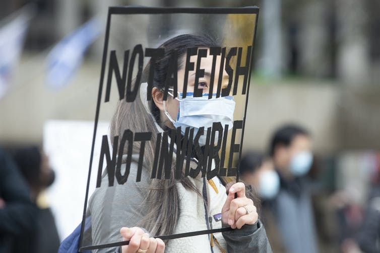 Woman stands holding protest sign