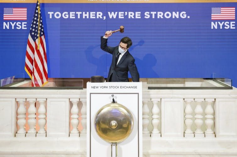 A man holding a gavel in the air above his head prepares to ring the closing bell at the New York stock exchange