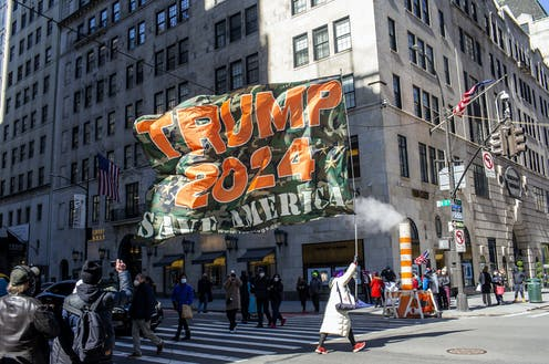 """Trump supporters carry a """"Trump 2024"""" banner in New York City."""