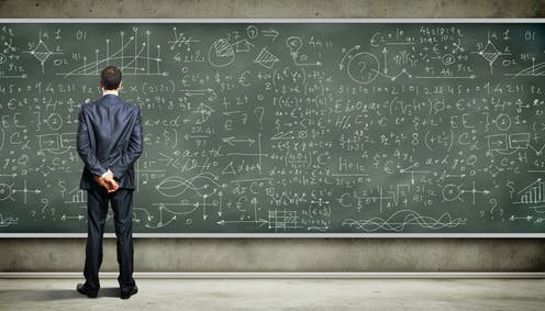 Businessman looking at complex equations on blackboard.