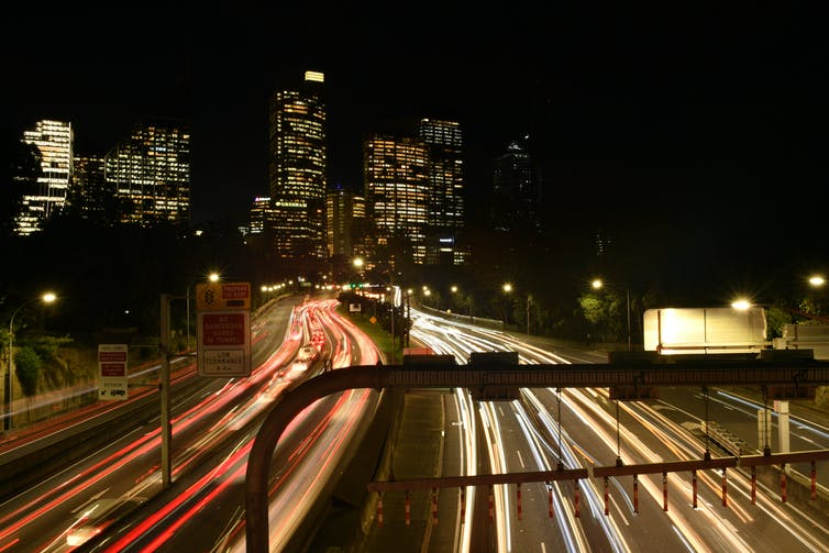 Sydney CBD skyline with headlights on the freeway.