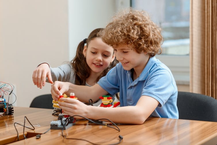 Boy and girl working on making a small robot.