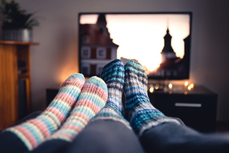 couple's feet in socks in front of a TC screen