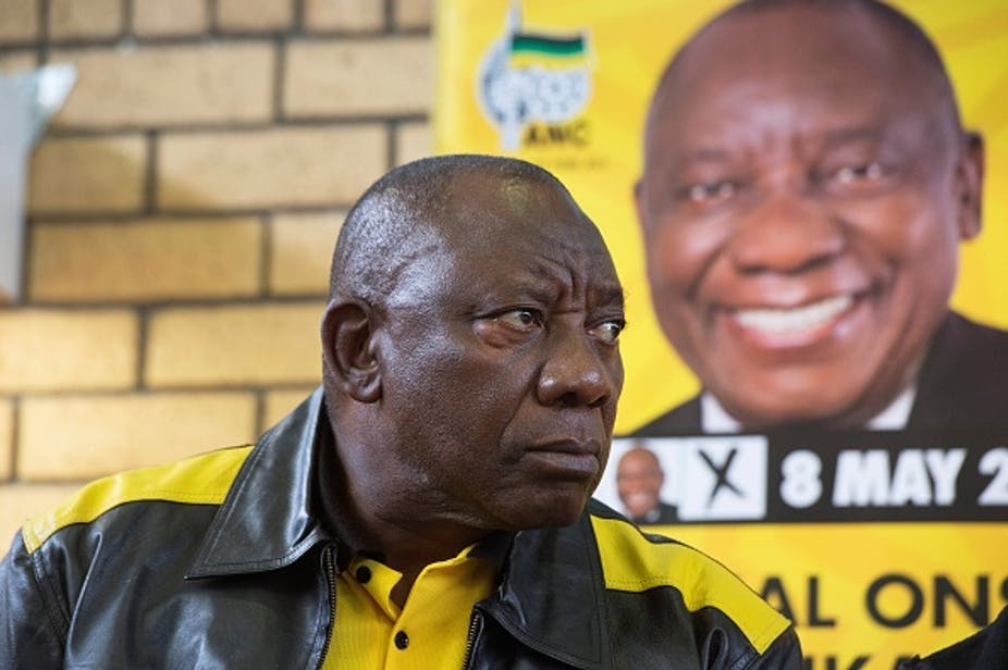 A man wearing a black and gold leather jacket and matching T.shiort gioves a stern look.