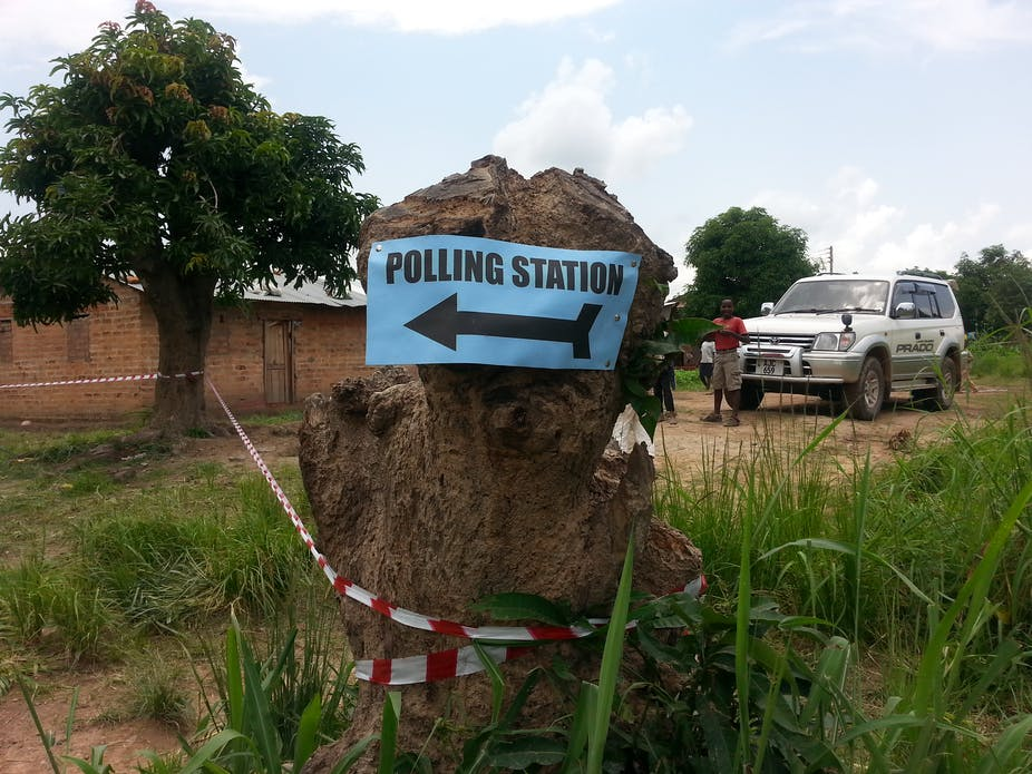 Sign for polling station fixed to a tree stump outside a rural building