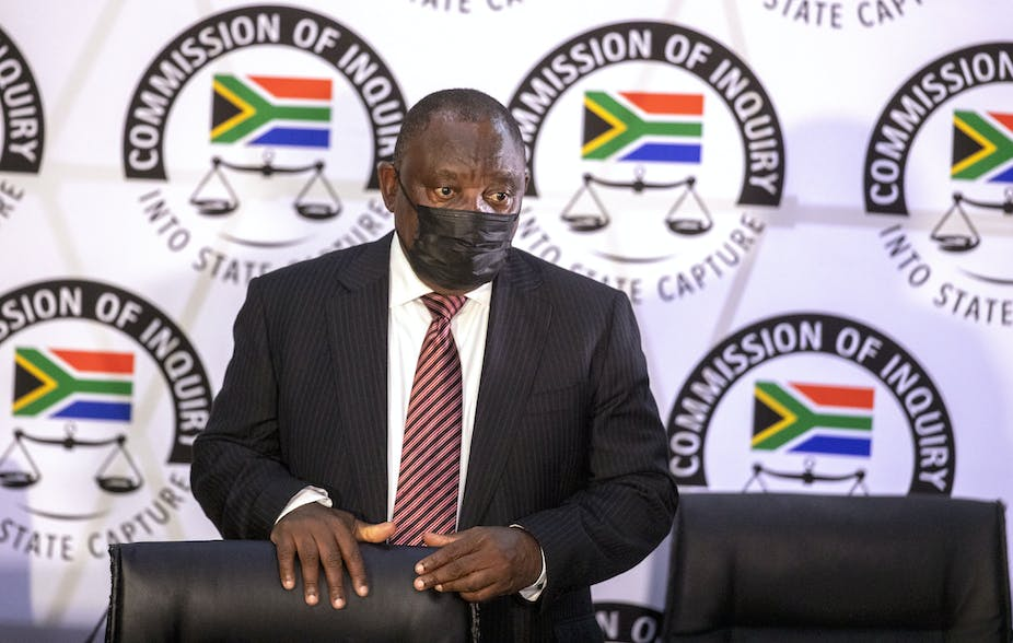 A man wearing a dark suit, white shirt, striped maroon tie and a black face mask stands behind a chair with the emblem of the South Africa's state capture commission in the background