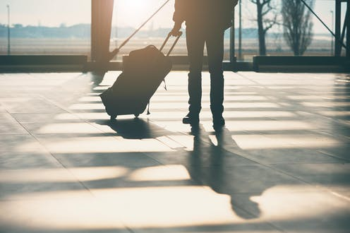 A passenger stands with a suitcase in an airport departure lounge.