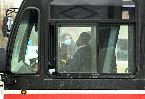A bus driver and a passenger seen through a bus window