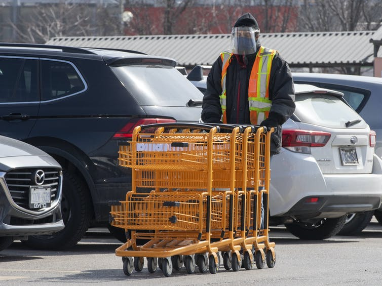 A person in a face shield pushing a row of shopping carts in a parking lot