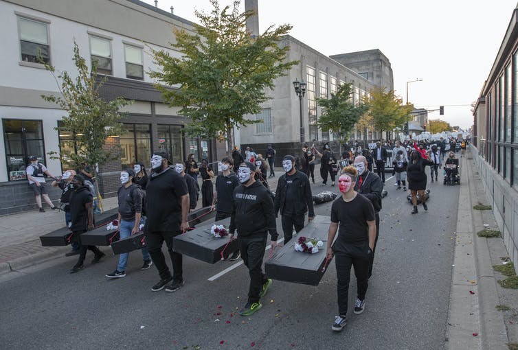 A crowd of people march, some carrying mock coffins