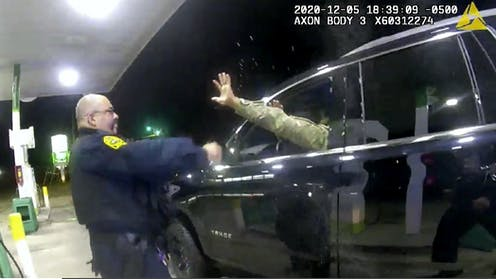 A police officer sprays a man sitting in the driver's seat of a car