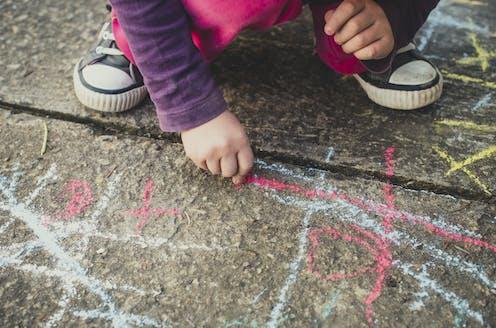 Un enfant dessine sur le sol avec une craie.