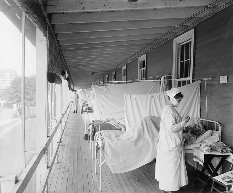 Black and white image of a nurse in a hospital ward
