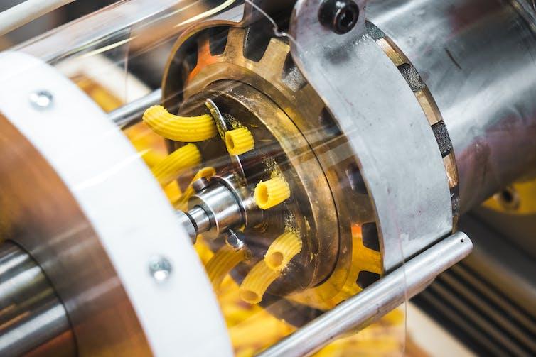 A bronze die machine extrudes pasta into a shape