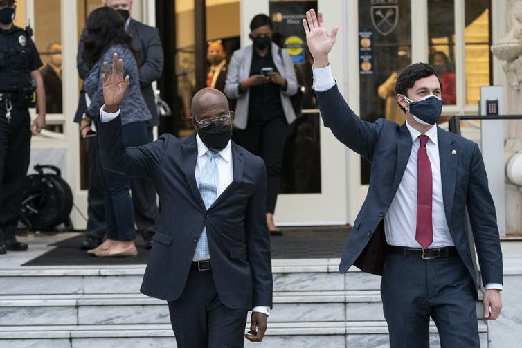 Two men in suits wave to a crowd