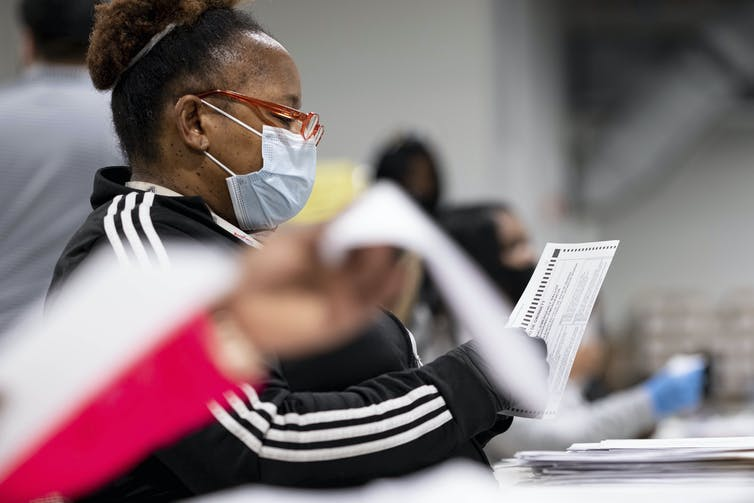 A woman in a mask handles papers