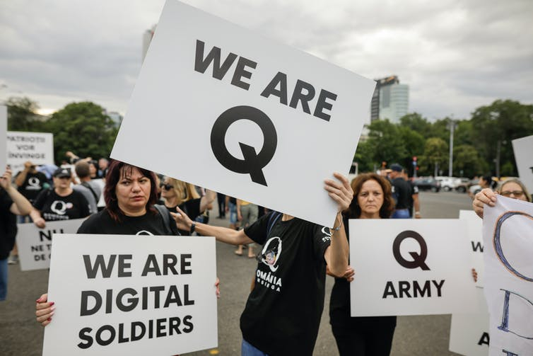People display Qanon messages on cardboards during a political rally