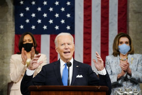 President Biden gesticulates with both hands as he speaks before Congress, flanked by Vice President Kamala Harris to his right and House Speaker Nancy Pelosi to his lift and an American flag draped behind him.