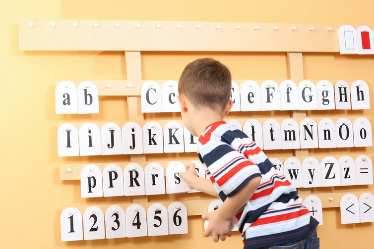 Boy pointing out letters.