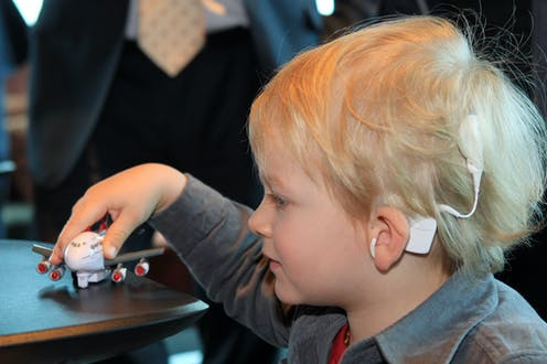 young boy with a cochlear ear implant plays with a toy plane