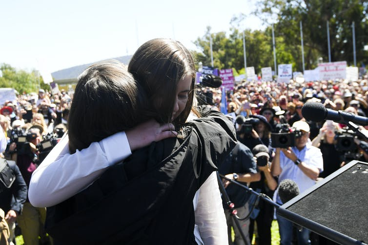 Brittany Higgins hugs an organiser at a protest.