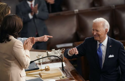 A smiling President Biden gestures to Vice President Harris and Speaker Nancy Pelosi after giving a speech to Congress