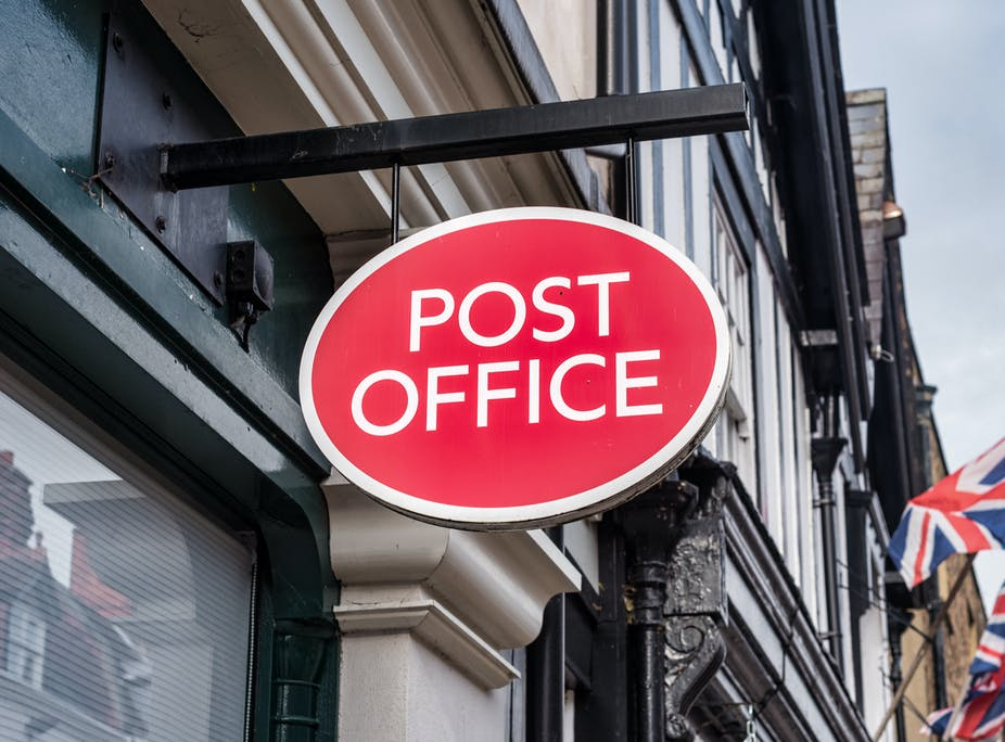 A Post Office sign hanging on a British high street