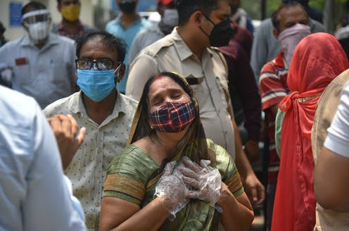 A woman with mask and gloves clutches her heart after hearing of the death of a family member, New Delhi, India, April 29 2021