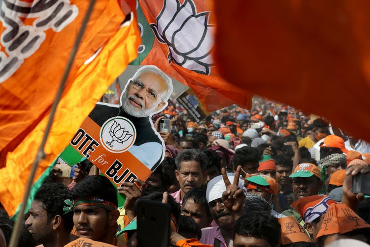 Mass rally of BJP supporters with flags and banners featuring Prime Minister Narendra Modi.