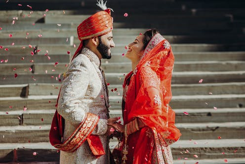 Indian couple on their wedding day, standing by steps surrounded by floating petals