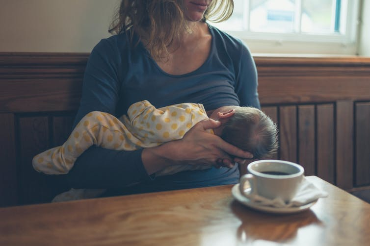 A woman breastfeeds her baby while having a coffee in a cafe