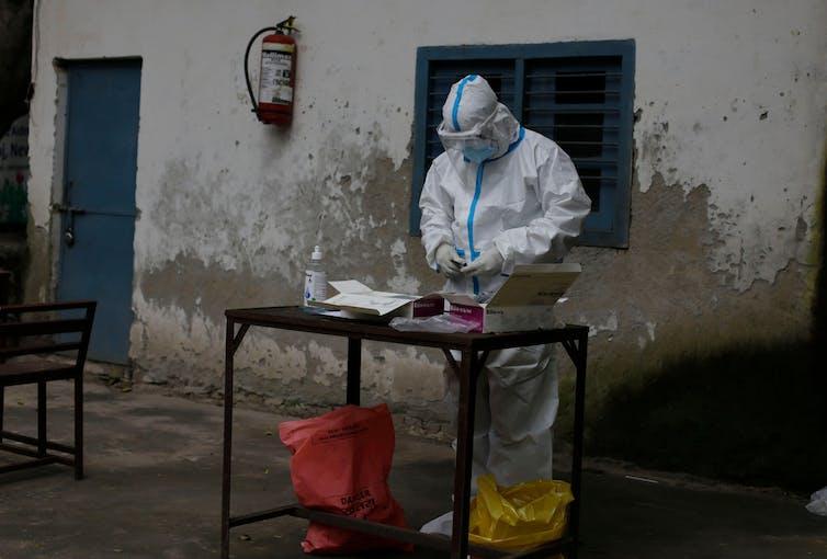 Médico preparando una prueba de COVID en una mesa exterior en Nueva Delhi