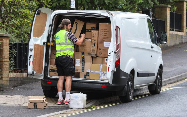 A delivery driver offloads boxes from a white van parked on the pavement