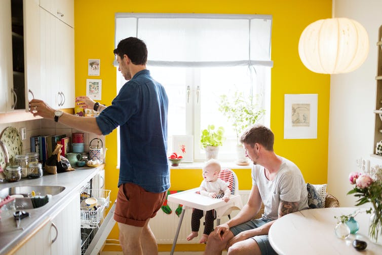 A gay couple prepare food in a yellow kitchen as a baby in a high chair looks on