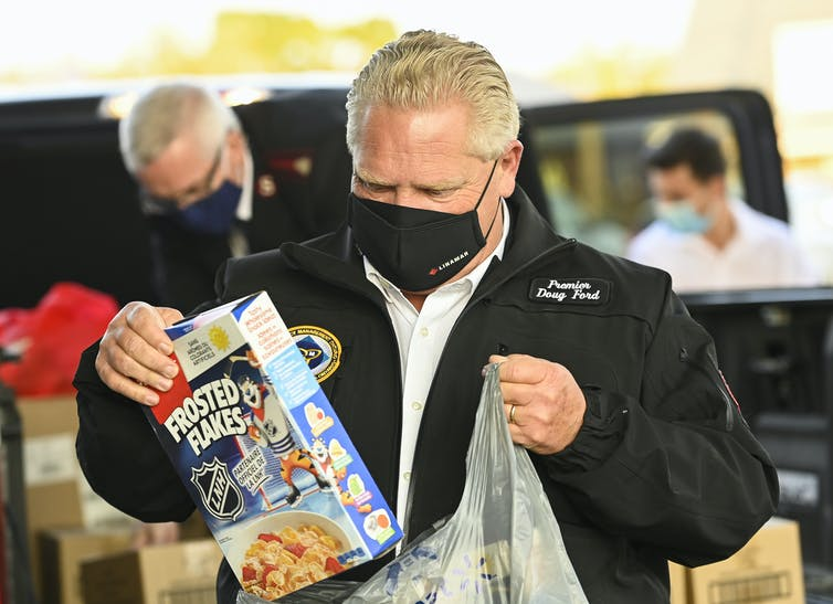 Ontario Doug Ford puts a box of Frosted Flakes into a plastic bag.