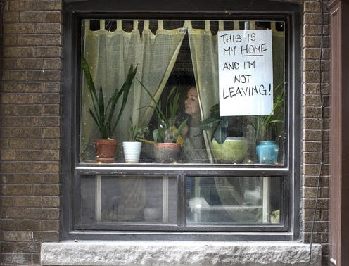 A woman looks through a window with a sign taped to it reading This Is My Home and I'm Not Leaving.