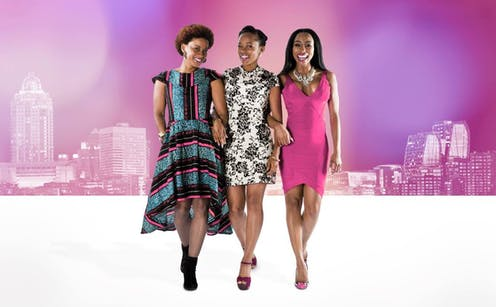 Three young women, brightly and stylishly dressed, link arms as they walk. Illustrated behind them, against a pink backdrop, a city skyline.