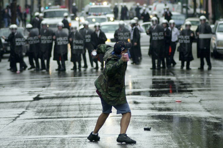 A protester throws debris at Cincinnati police officers in riot gear in 2001.