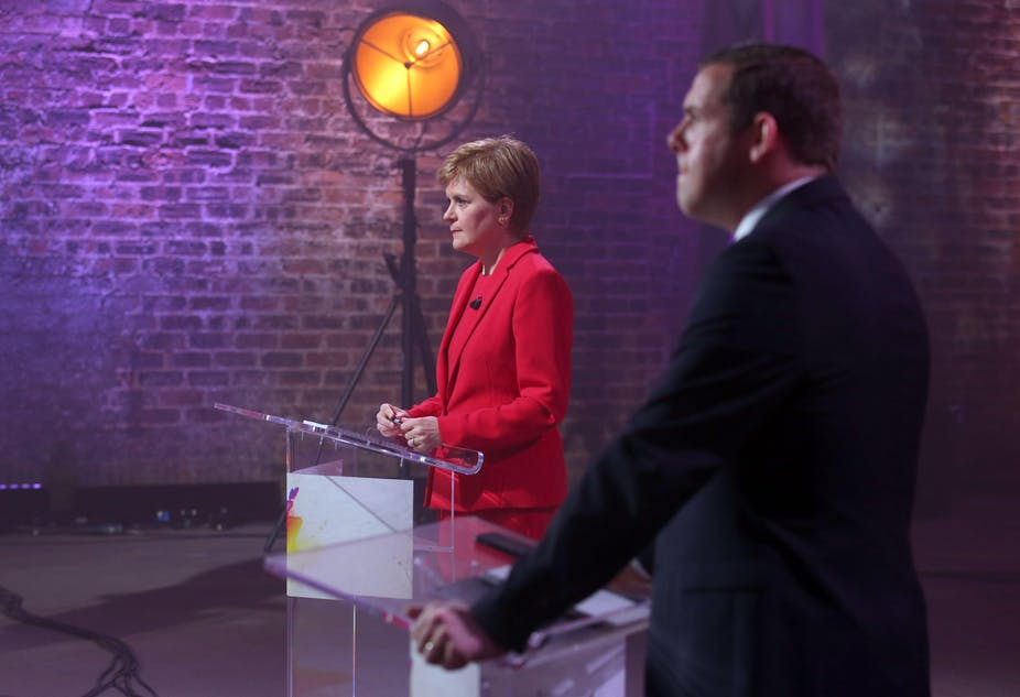 Nicola Sturgeon and Douglas Ross stand behind podiums during televised election debate.