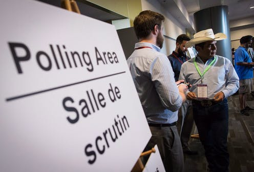 People stand outside polling area