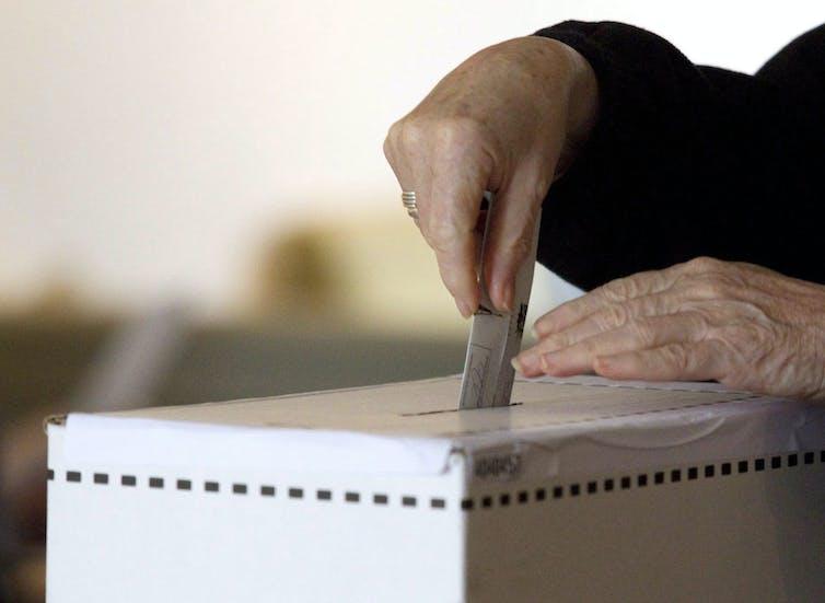 Woman casts vote in ballot box