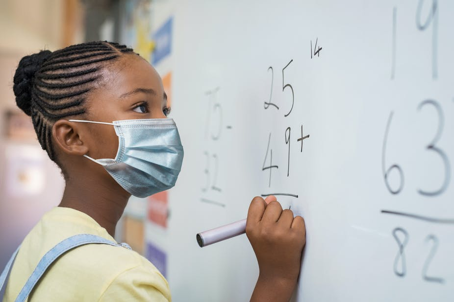 Young Black girl standing at a white board, working on a math problem.