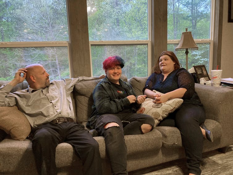 Andrew Bostad, a transgender youth, sitting on the sofa at home with his mother and stepfather.